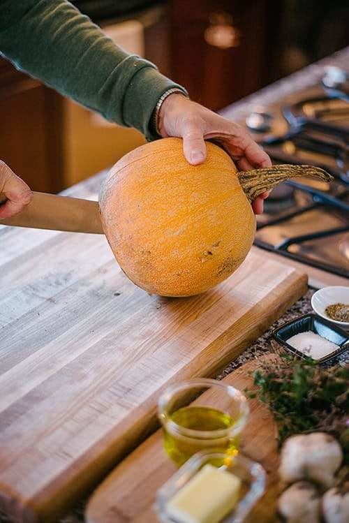 hands with knife cutting a pumpkin in half on a cutting board