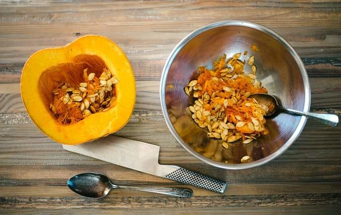 half a pumpkin and bowl with seeds, knife, spoon, on a cutting board