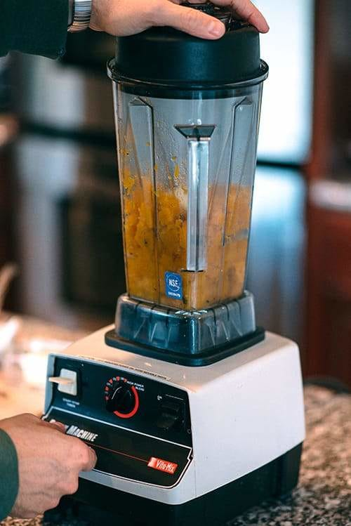 blender with pumpkin puree and hand pressing button