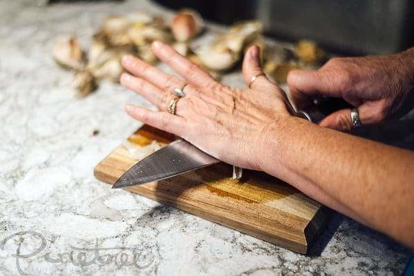 smashing garlic with a knife on a cutting board in the kitchen
