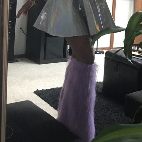 Jasmine from the waist down wearing a shiny silver skirt showing off lilac colored furry leg warmers.