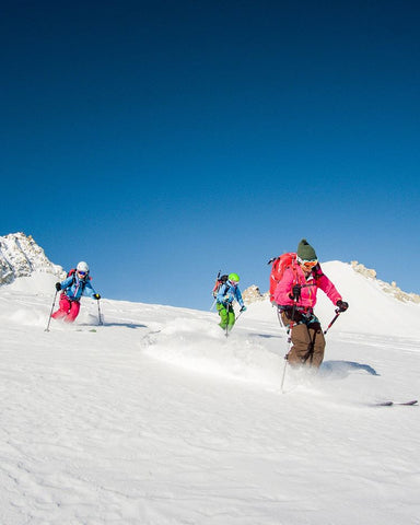 3 women skiing in powder