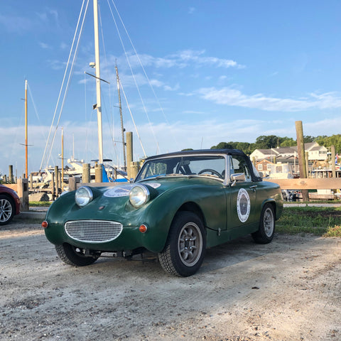Austin Healy Sprite in front of boats