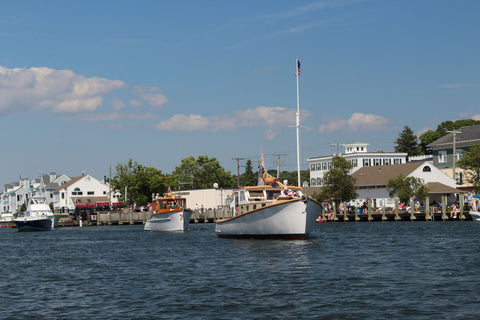 antique boats heading down the mystic river