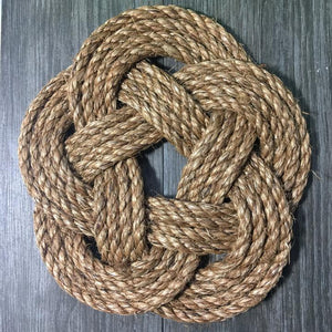manila woven trivet turkshead tied flat with a slate background