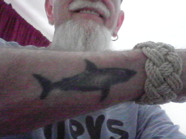 An old salt shows off his Turks Head bracelet and shark tattoo