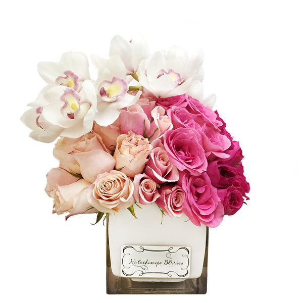Ombre floral arrangement from light to dark pink set in square cube vase