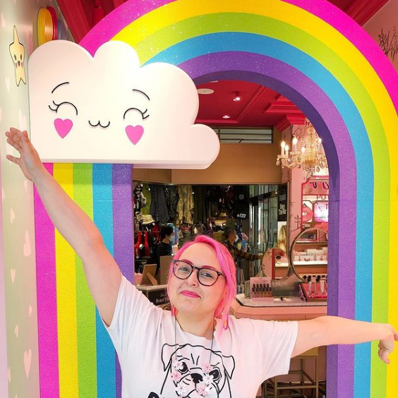 A picture of Sophie with her arms outstretched and a big happy smile, stood in front of a colourful rainbow and cloud mural