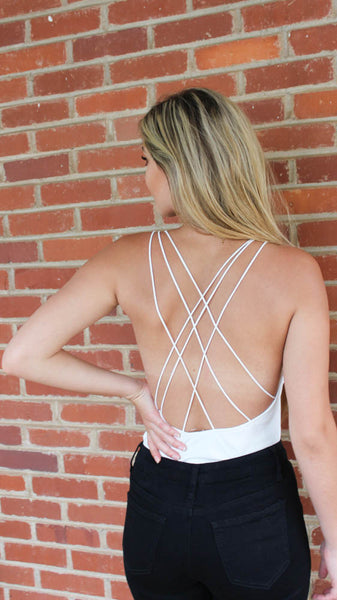 white deep cut body suit with strappy back