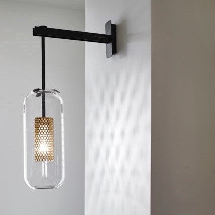 Vadim wall light has been designed by Maison Sarah Lavoine. The generous size of the glass bulb contrasts with the delicate golden perforated cage floating inside and the strict elegant lines of black metallic arm