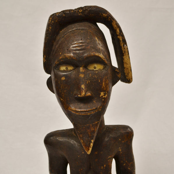 Nude African man carving face