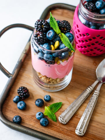 Two mason jars with yogurt, granola, and berries garnished with mint.