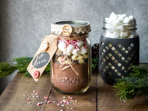 Two Mason jars are filled with the ingredients to make hot cocoa, including marshmallows and peppermint.