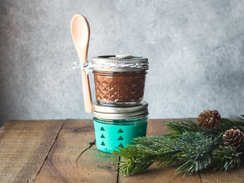 Two small Mason jars are stacked on top of each other and filled with homemade Nutella.
