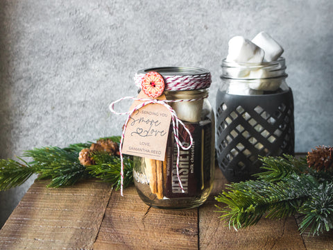 A mason jar filled with Hershey's bars, marshmallows and graham crackers and decorated with a gift tag and festive twine.