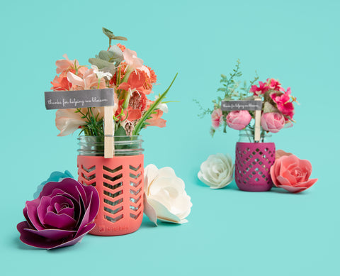 16oz mason jars adorned with JarJackets silicone mason jar sleeves and containing fresh spring flowers in pinks and coral colors.