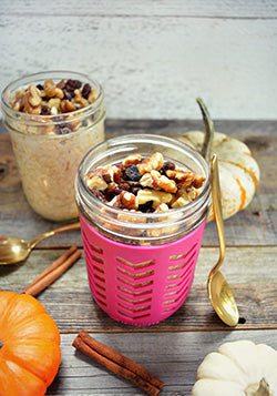 Pumpkin spice oatmeal topped with nuts and raisins in a mason jar.
