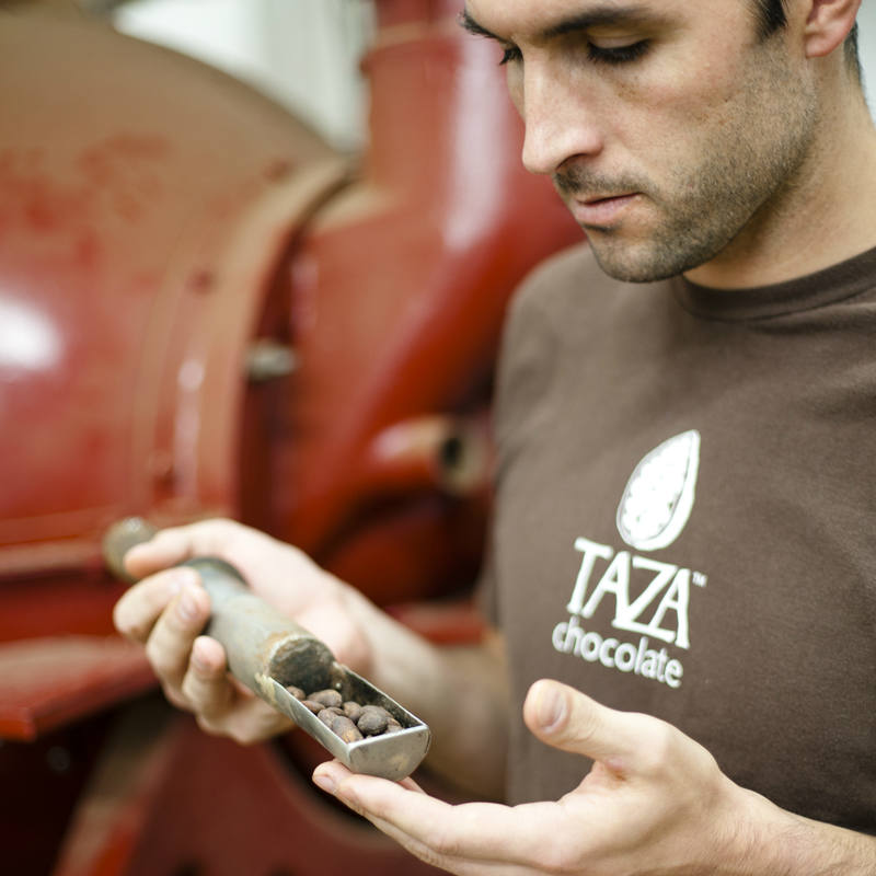 Taza Chocolate founder, Alex Whitmore, checking cacao beans during a roast
