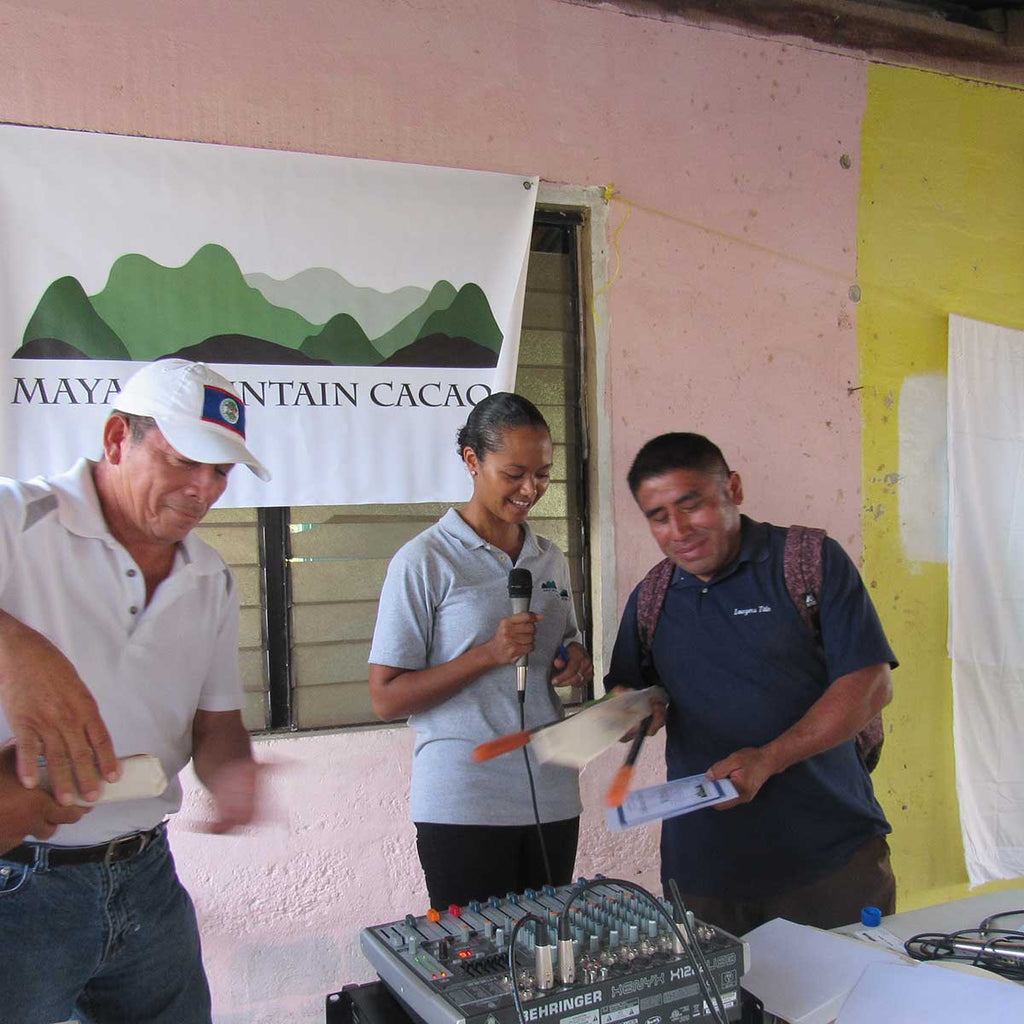 Maya Mountain Cacao's Minni Forman awards a farmer a prize for good growing practices