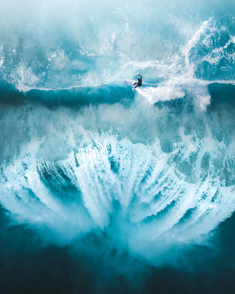 Phil de Glanville's photography aerial capture of a surfer by a waterfall in Australia