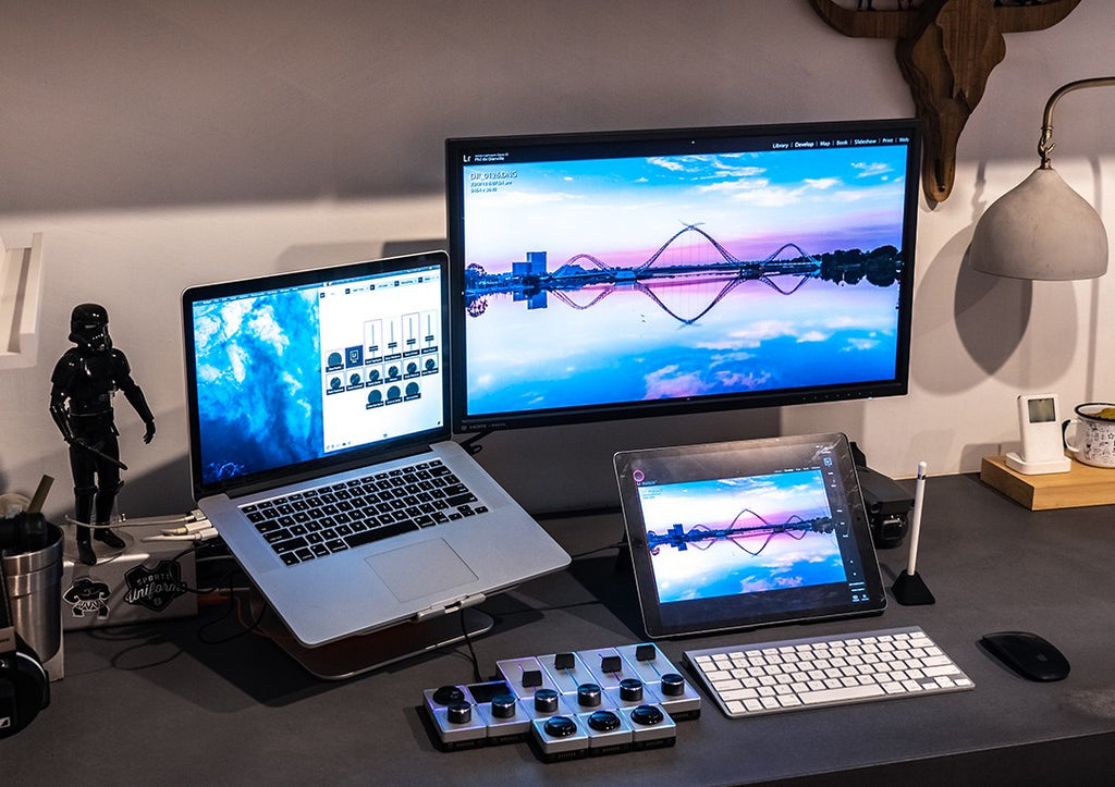 Image of a desk showing a photographer's workspace setup with a macbook, tablet, computer monitor and Palette Gear tactile, precision controller
