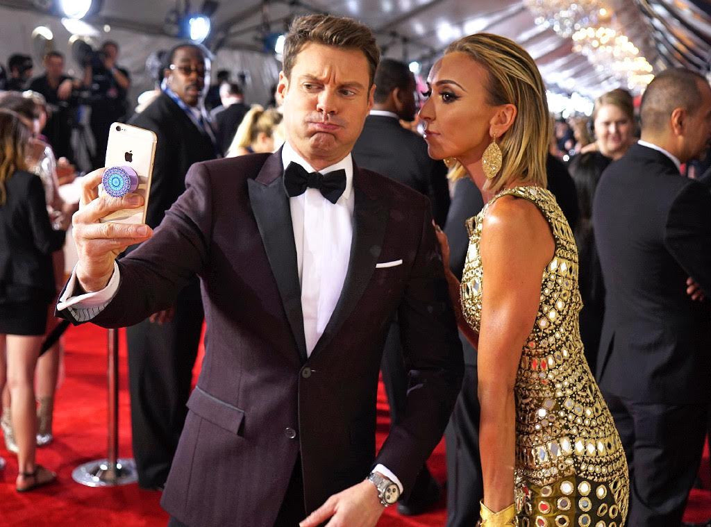 Ryan Seacrest and Giuliana Rancic take a selfie with a PopSocket