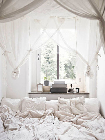 White on white Scandinavian bedroom with ivory white curtains