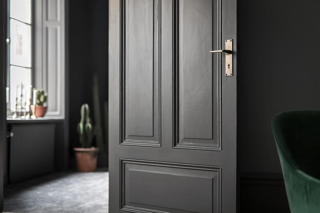 Beautiful dark interior door in moody Swedish apartment