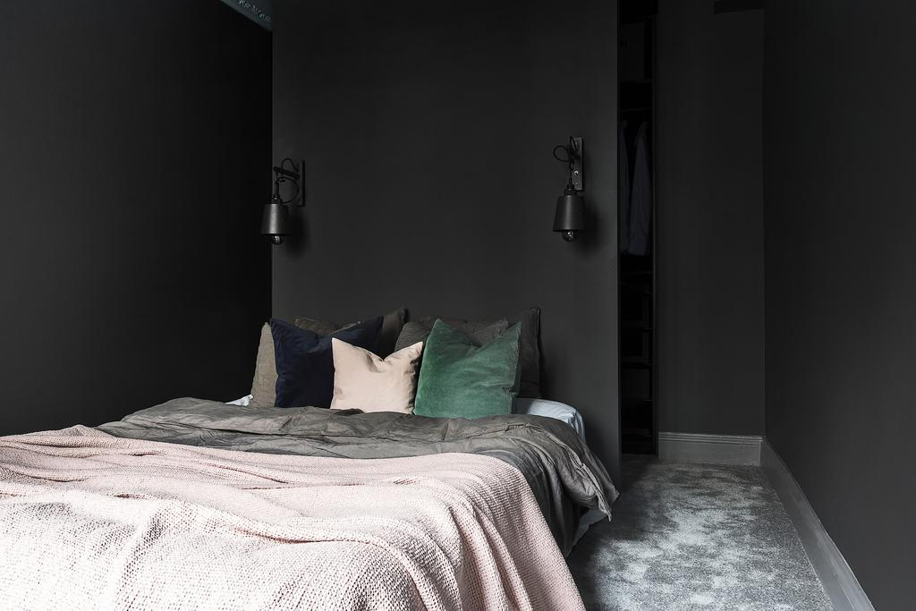 Bedroom with black walls in moody Swedish apartment