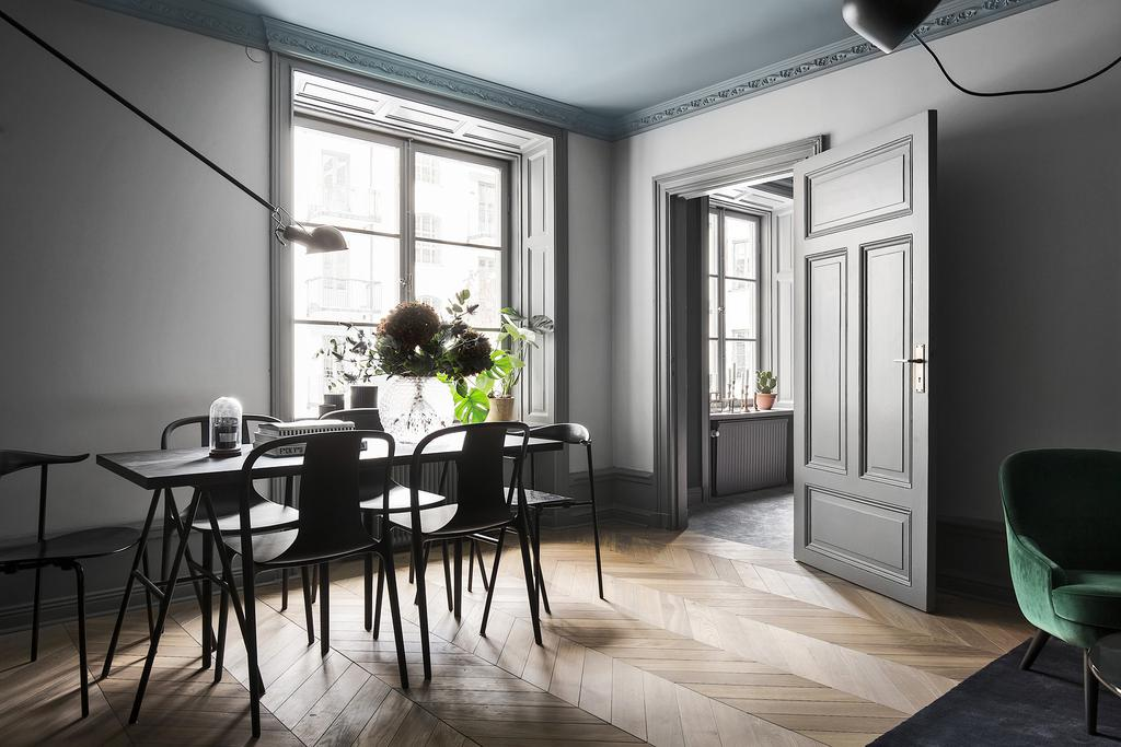 Swedish style in dining area of apartment with moody greys