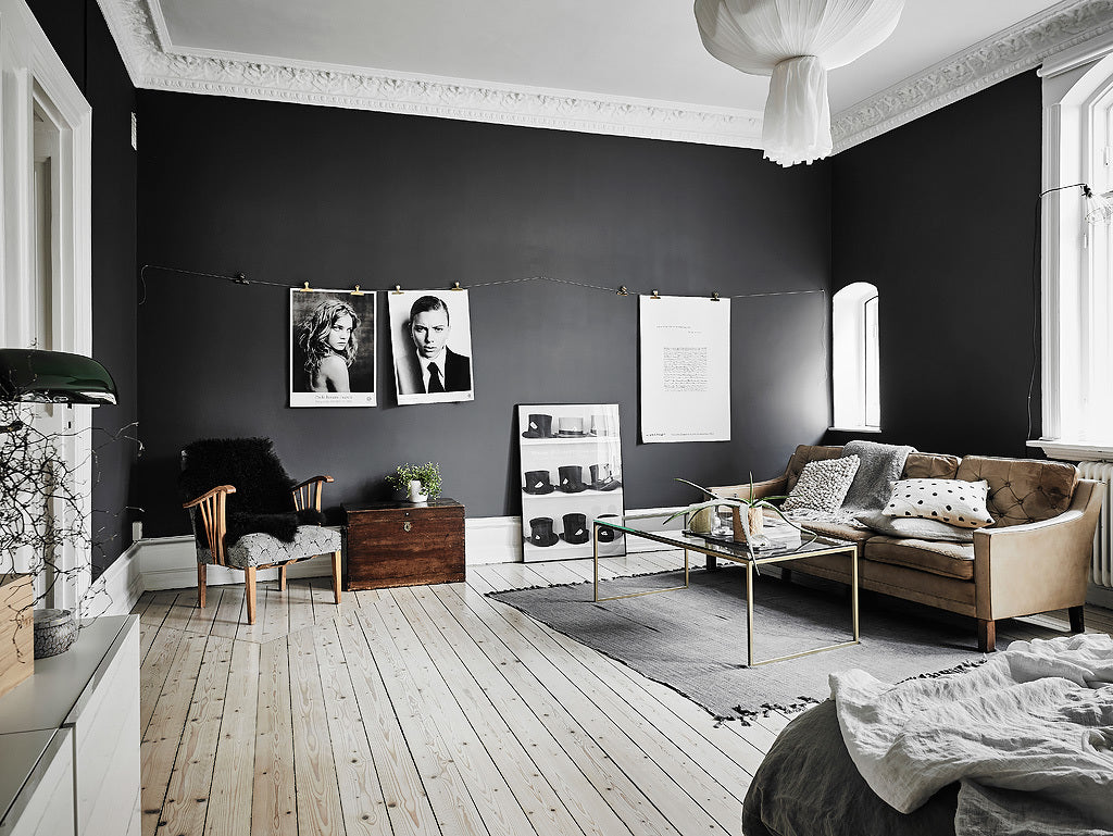 Prints hung on a wire with in Gothenburg apartment with stunning dark walls