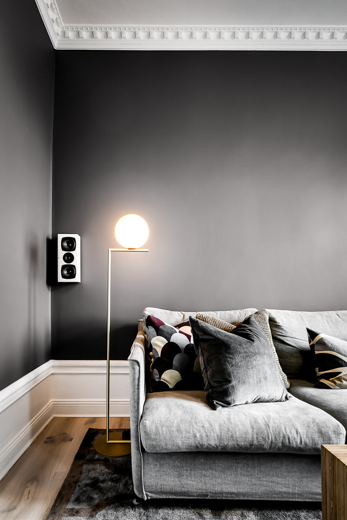 Cosy corner of Swedish living room with dark grey walls