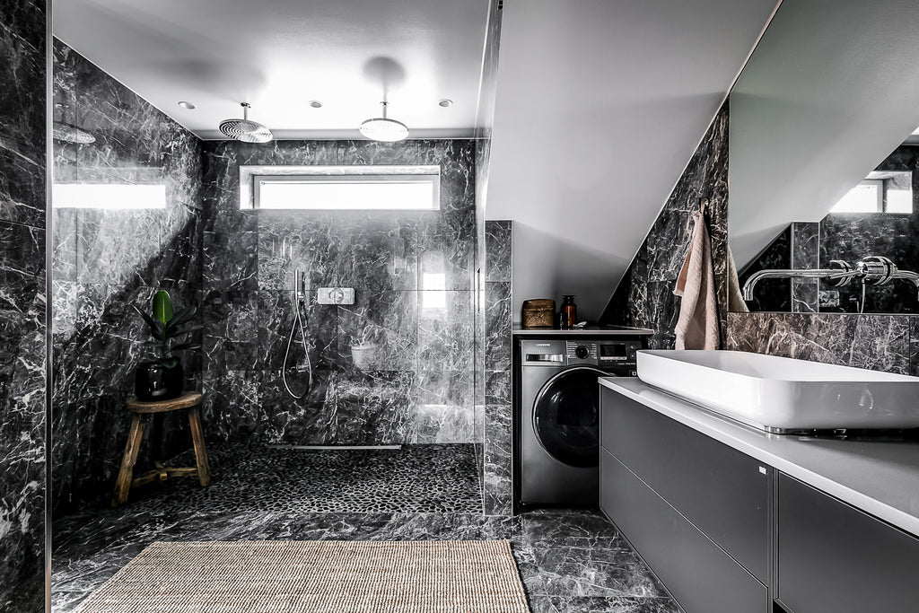 Black marble creates a dramatic bathroom in Swedish home