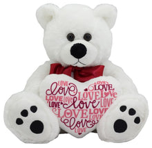 "Large white teddy bear with black padded paws holding a large heart with lots of ""love you"" words written over it"