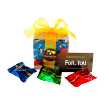 Brightly coloured individual pieces of fudge inside a gift box with ribbon