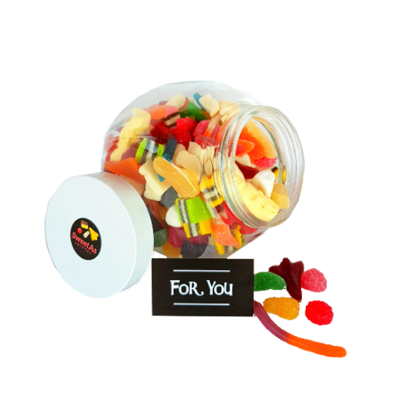 Large lolly jar filled with mixed lollies, bright colours and spilling over with sweets