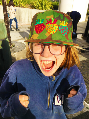 woman gaviota strawberry by harry's berries camo hat front santa monica farmers market final