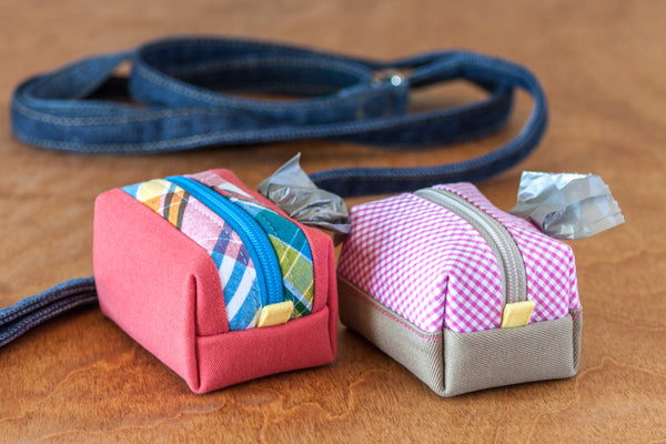 Colorblock poo bag dispensers made with reclaimed materials in gingham and plaid
