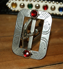Metal belt buckle with one red glass jewel at top and bottom of buckle.