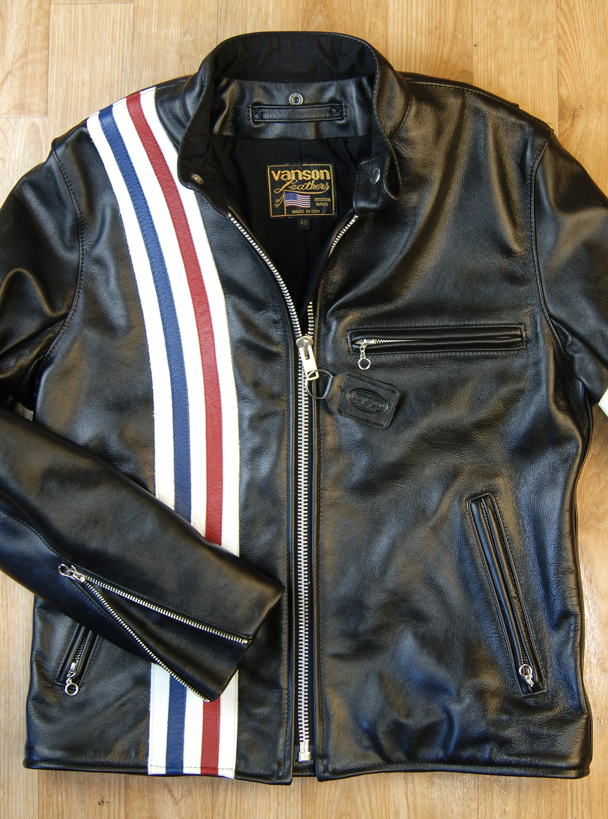 Front of black leather motorcycle jacket.  Right side stripes of red, white and blue.  Left side chest pocket and handwarmer pockets, all with ring pull zippers.