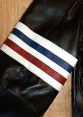 Close-up of red, white and blue stripe armband on right bicep.