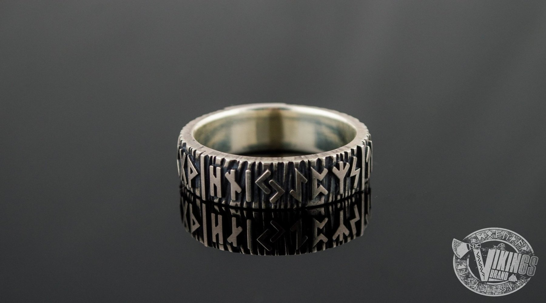 Elder futhark runes carved in a silver Viking ring on black background.