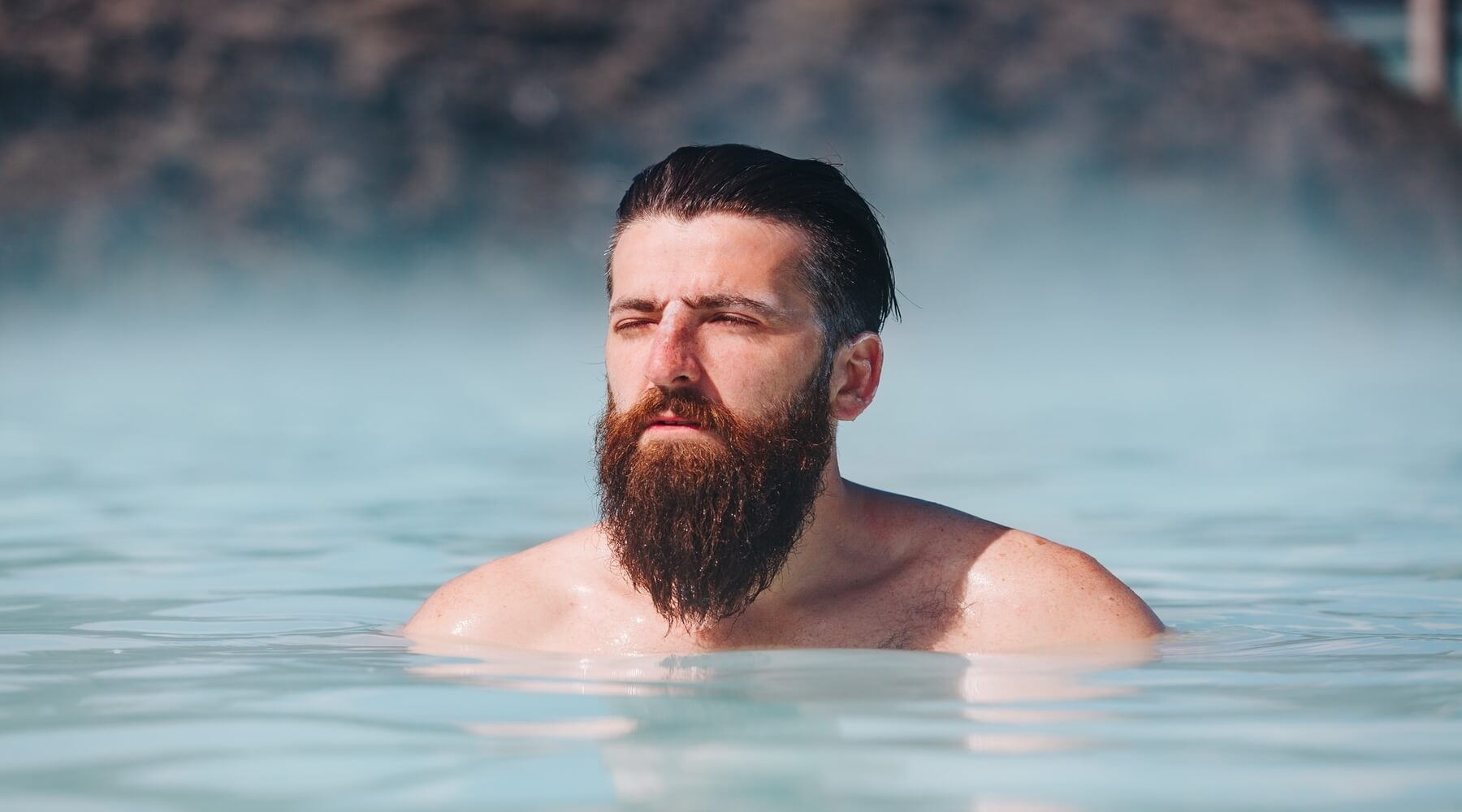 A Viking with a full beard in a hot spring