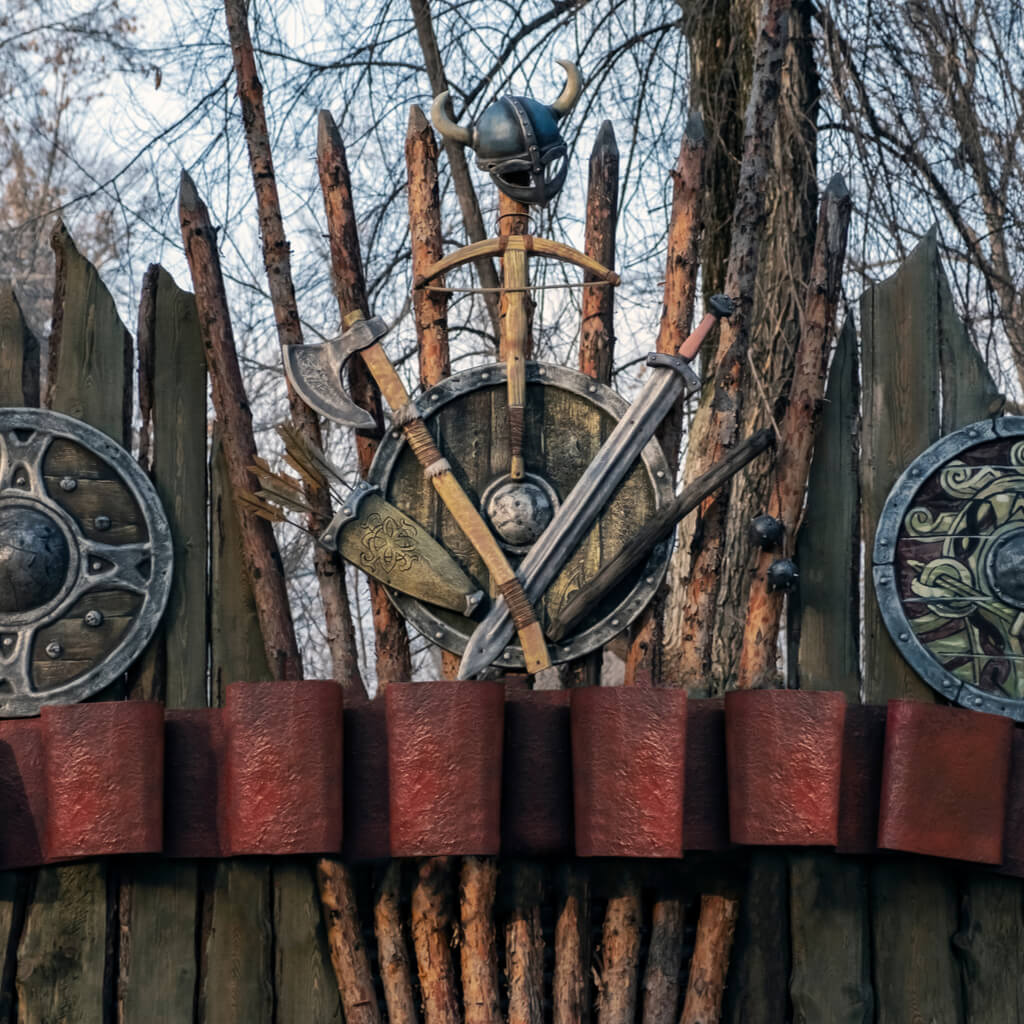 Wooden fence with shields, axes, swords and helmets