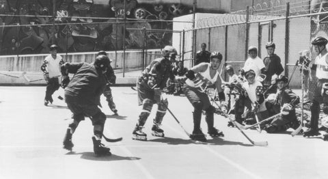 Mighty Ducks play outdoor roller hockey on what looks to be a tennis court likely somewhere in California. old school rollerblades, pads and other equipment are seen