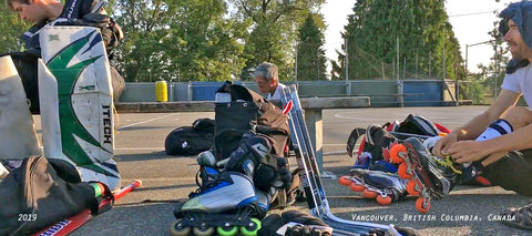 suiting up for outdoor street roller hockey in Vancouver BC at Queen Elizabeth Park. Marsblade and Bauer skates with some shafts and abs blades on the bench.