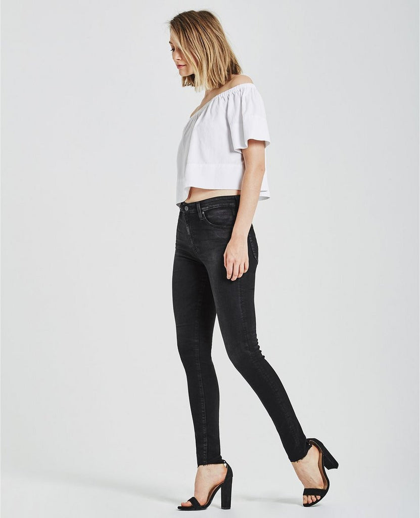 Woman model seen from left side, wearing black high-rise skinny jeans feature a washed-down finish and raw hems. Size 27.