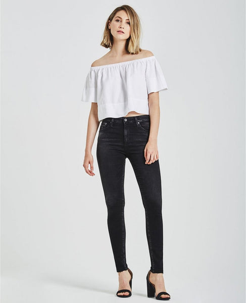 Woman model wearing black high-rise skinny jeans feature a washed-down finish and raw hems. Size 27.