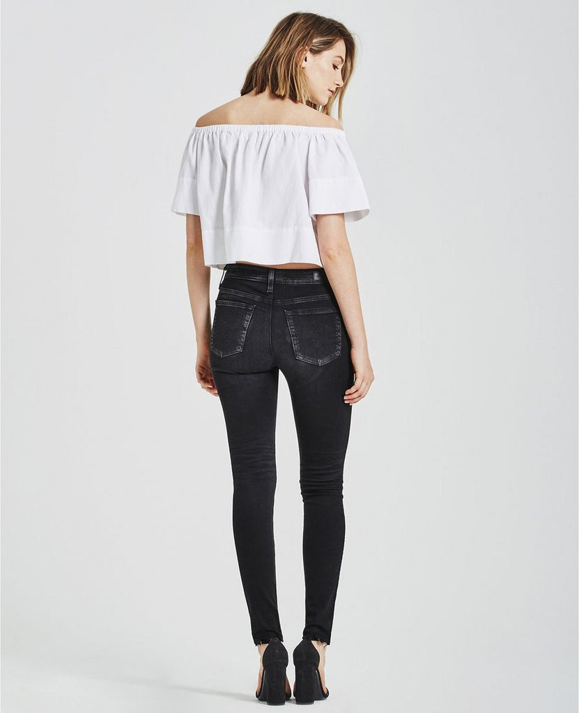 Woman model wearing black high-rise skinny jeans feature a washed-down finish and raw hems, from back view. Size 27.