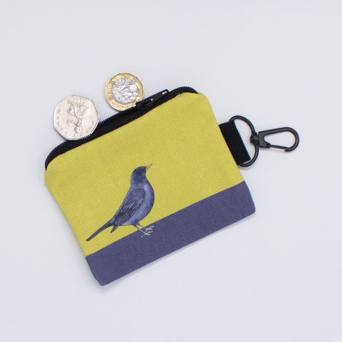 A key fob in the form of a purse with a blackbird design